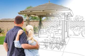 a couple looks at their plans for a pergolas in their home built by Townsville Carports